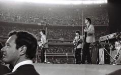 Brian Epstein observa a plateia, com os Beatles ao fundo